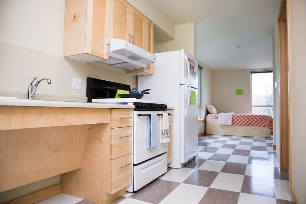 New studio apartment with light-colored wood cabinets, white stove and refrigerator, white and gray checkerboard flooring and a bed with red and white wavy stripe bedding.