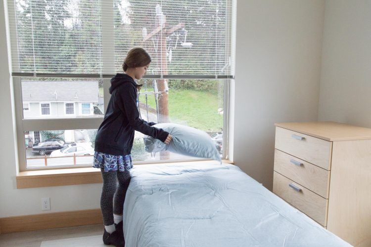 Volunteer fluffs pillow over new bed at The Estelle housing