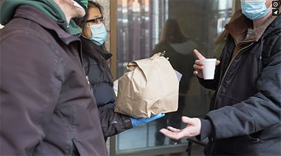 A person in a face mask hands a filled brown paper bag to another person in a face mask.
