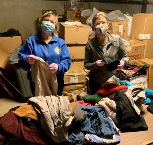 Two members of PSONS sort and organize clothing