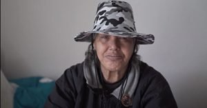 A woman wearing a gray, black and white camo pattern hat, and gray and black jacket looks directly into the camera.