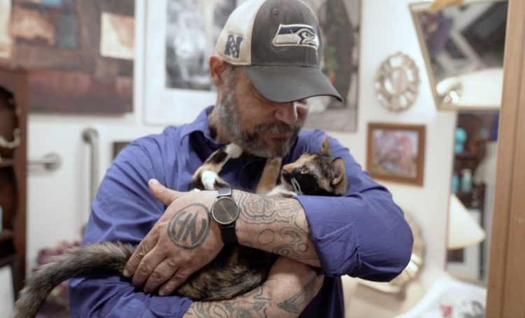A bearded man in a blue shirt and a Seahawks cap looks down at the cat he holds in his arms.