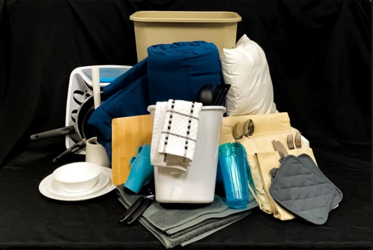 An assortment of housewares, including a garbage can, cup and saucer, drinking glass, towels, kitchen towels, cutlery, hot pads, sheets an more.