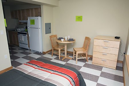 A view from the right of the end of a bed covered with a gray-and-red-striped comforter, to a light-colored bistro table, chairs and chest of drawers, and part of a kitchenette, with refrigerator and stove.